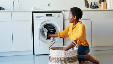 Woman doing laundry in her kitchen at home