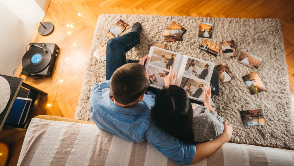 Newlyweds are looking at wedding photo album together