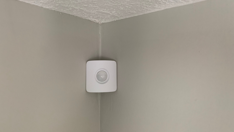 A SimpliSafe motion sensor hangs in the corner of a gray wall.
