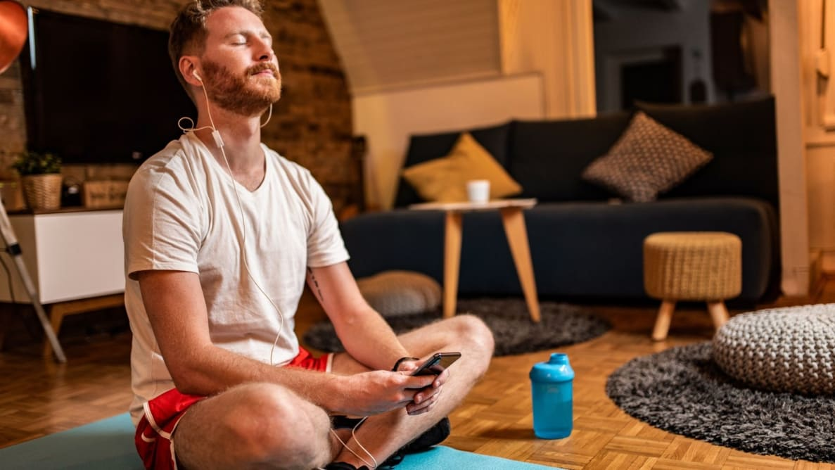 a person sits on a yoga mat holding their phone and listening to audio as though they're meditating