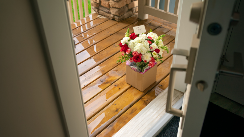 Flower arrangement sitting on ground on porch with front opened.
