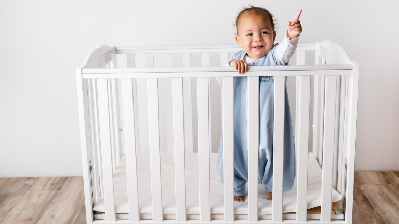 A baby stands inside a crib wearing a blue onesie.