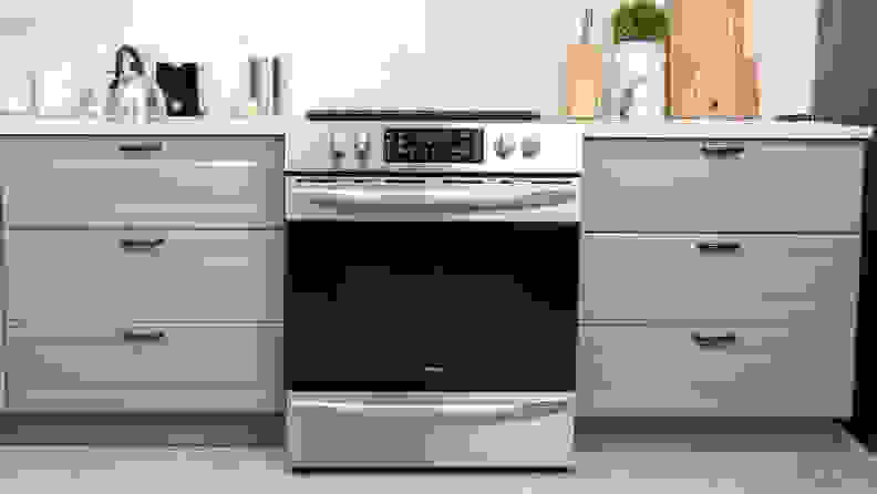The Frigidaire FGEH3047VF electric range installed between two grey kitchen cabinets.