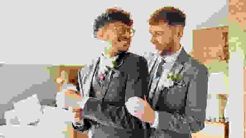 Married LGBTQ+ couple standing and looking at each other on their wedding day. They are dressed in suits and smiling.