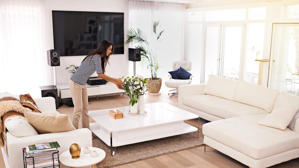 Woman tending to a plant in a bright living room