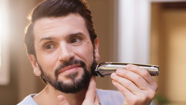 A man shaves his beard with a Wahl beard and nose trimmer.