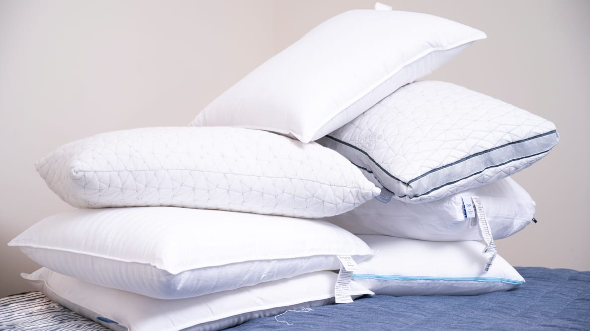 a pile of pillows including the casper, coop, brooklinen and amazon basics on a bed