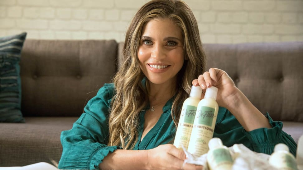 Danielle Fishel holding shampoo and conditioner bottles from her haircare line