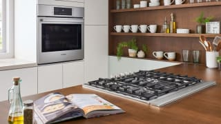 A lifestyle image of a gas cooktop and a corresponding wall oven in a brightly lit modern kitchen.