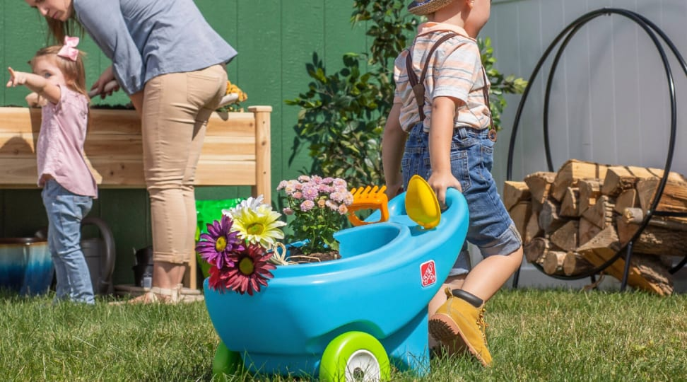 A child pulls a toy wheelbarrow full of plants