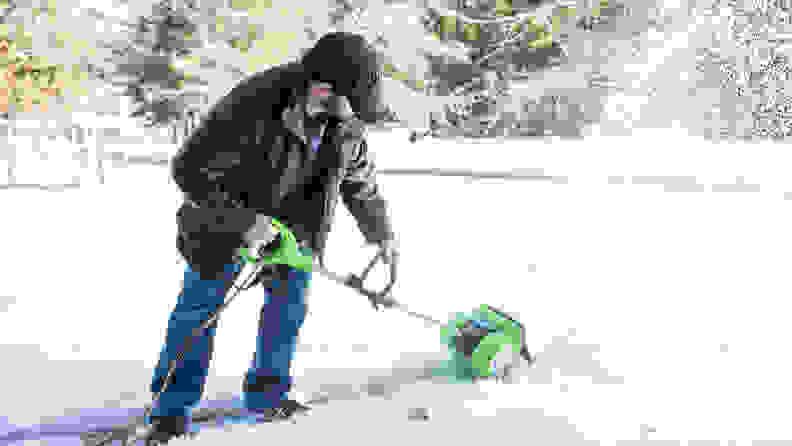 A man clears a path in the snow using the Greenworks Corded Snow Shovel