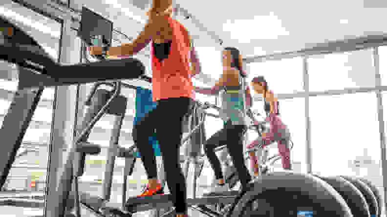 Three women using elliptical machines at the gym.
