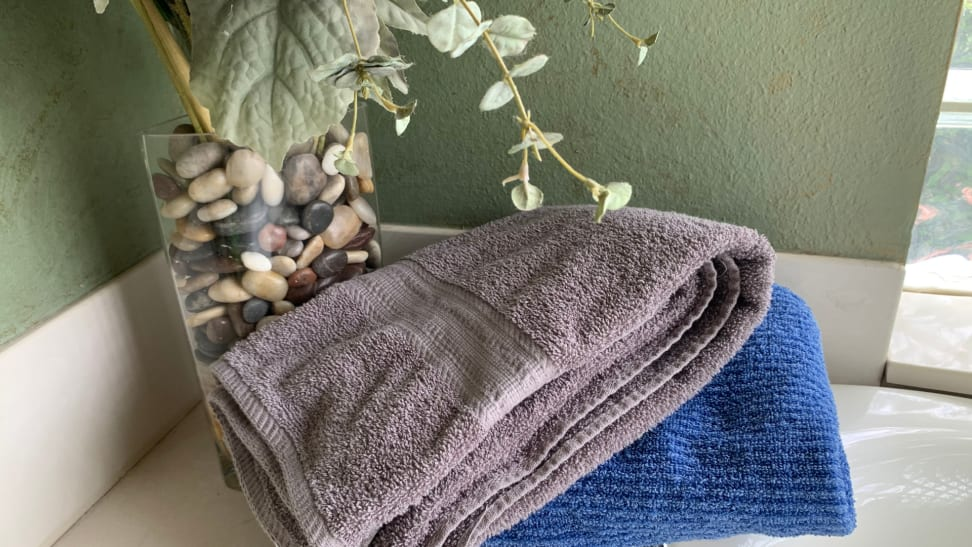 Two The Big One bath towels—one gray and one blue—sitting on a bathtub next to a plant