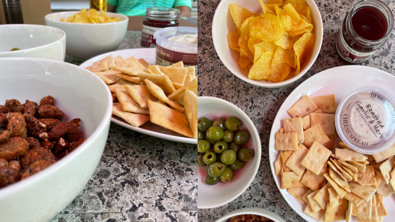 Bowls of chips, crackers, olives, and nuts sit on a counter.