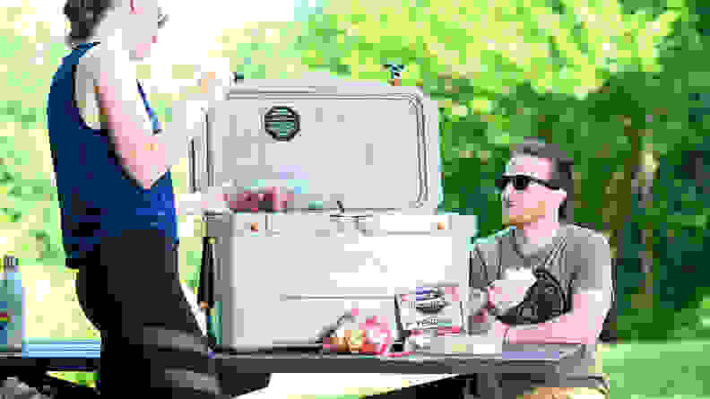 A man and woman with an Ozark Trail Cooler, sitting at a picnic table.