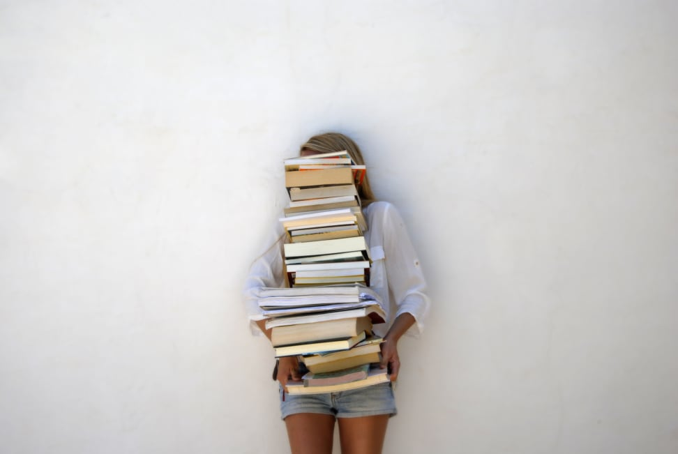 A woman carries a stack of books