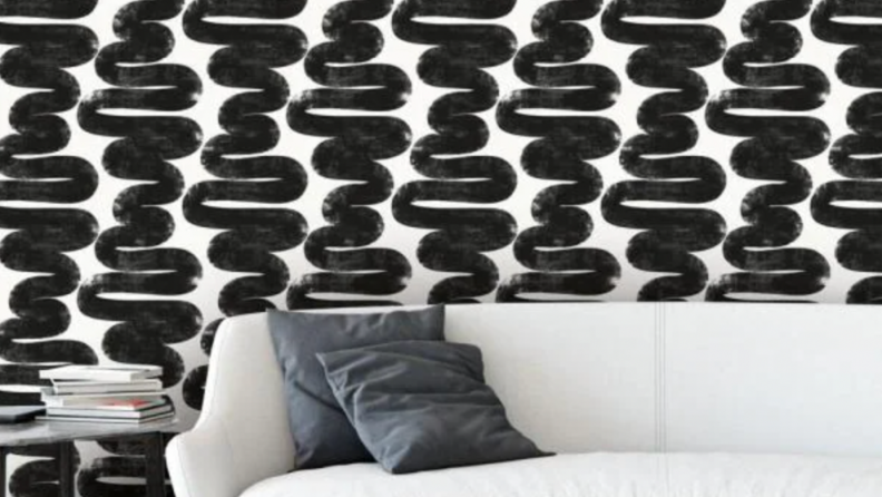 Black wavy lines are against a white background make up this wallpaper that's pasted on the walls behind a white couch.