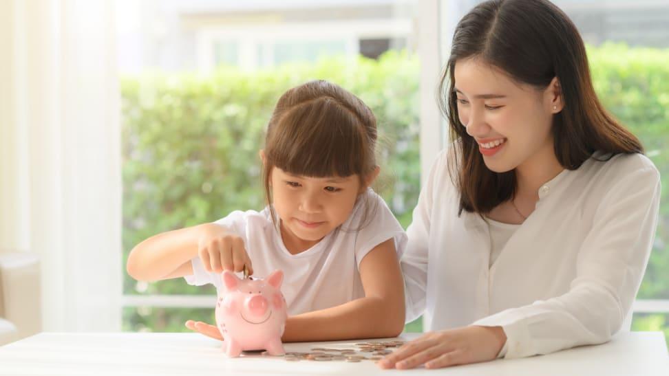 A child and parent put money into a piggy bank.