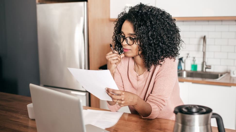 A woman wearing eyeglasses sits at a kitchen island looking over a piece of paper