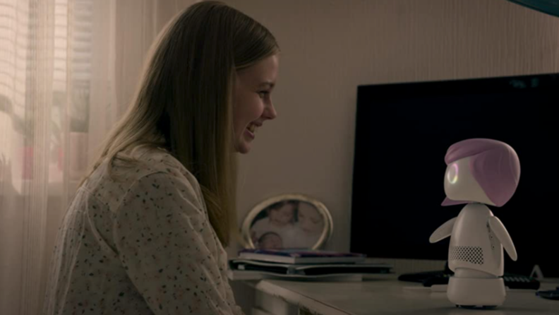 A still from 'Black Mirror' featuring a teen girl interacting with a sentient robot.