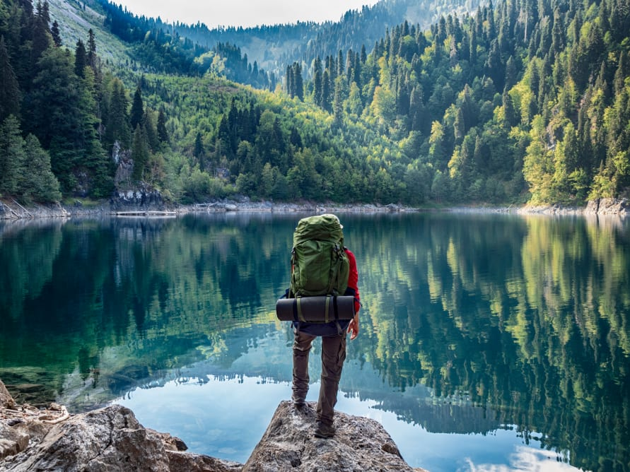 A hiker overlooks a beautiful body of water surrounded by hills and trees.