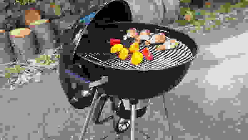 A charcoal grill with meat and vegetables on it.