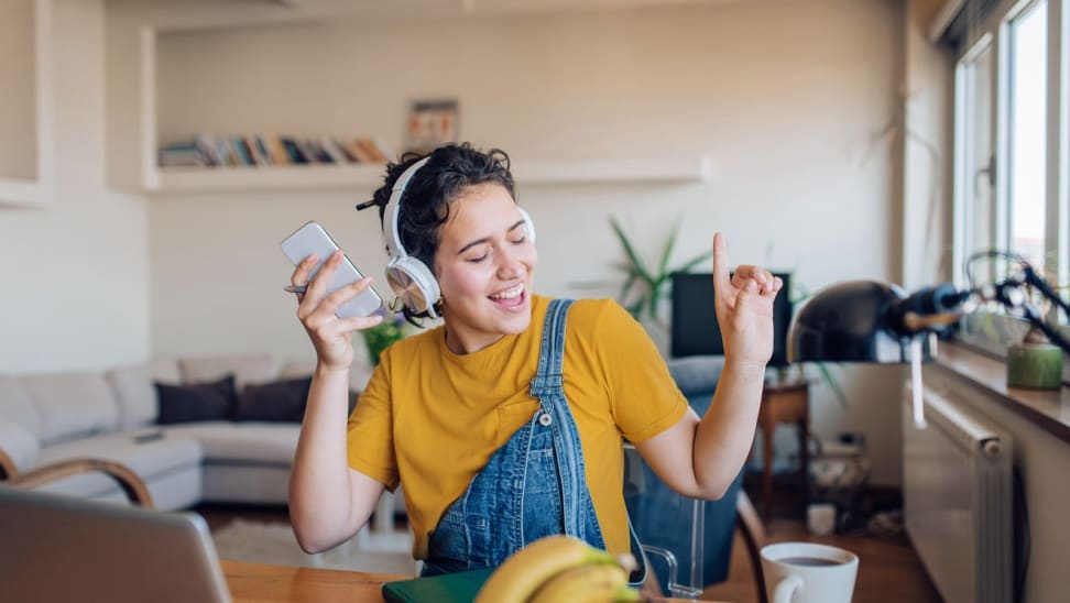 Woman wearing yellow shirt and overalls, sitting in living dancing to music while wearing headphones and holding smartphone.