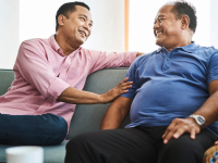 Two older people sitting on couch together while smiling and enjoying a conversation.