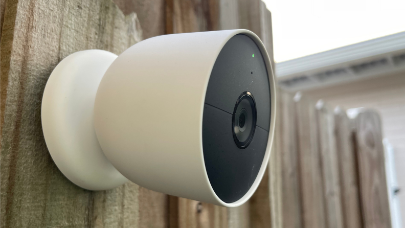 The Nest Cam (battery) hangs on a wooden fence.