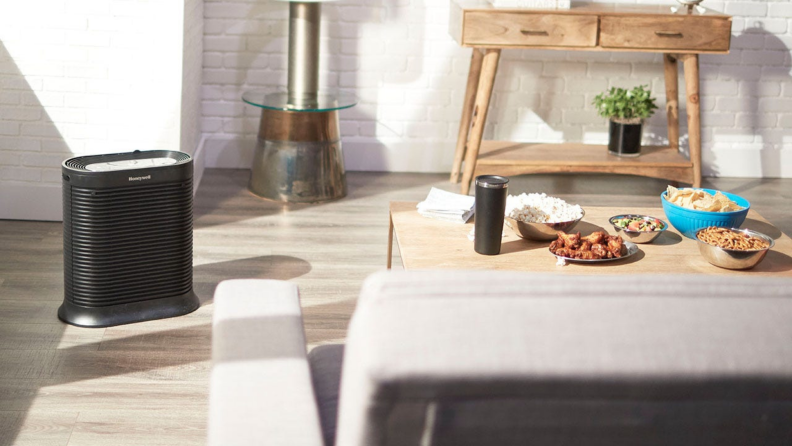 A Honeywell air purifier sits on the floor of a living room.