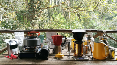 On an outdoor kitchen table, there are some coffee and cooking gadgets. From the left, there's a bag of coffee beans, a stove with a kettle on top, a bialetti moka pot, a pour-over coffee set up, and a milk jug.
