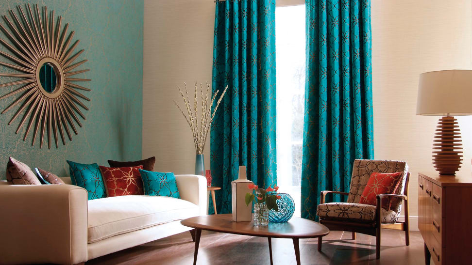 A living room decorated with blue curtains, sofa, coffee table, sun decor, and more.