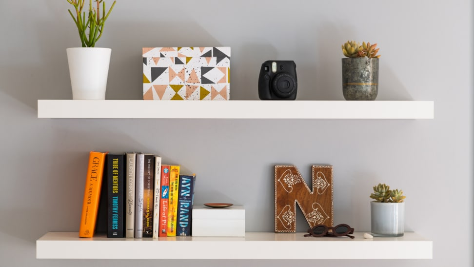 Decorations including a plant, jars, books, and boxes sit on two floating white shelves on a grey wall.