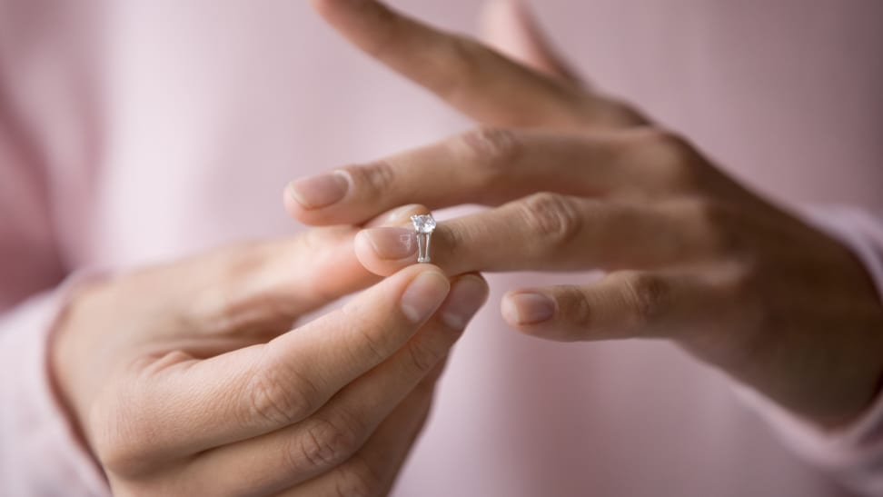 A close-up of a white person's hands, and removing a diamond engagement ring.