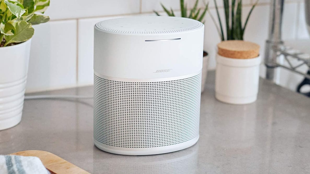 Silver and white Bose Home 300 smart speaker on kitchen counter with plants and cutting board