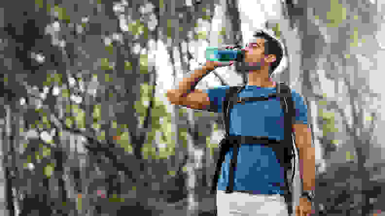 A man drinking from a water bottle on a hike.