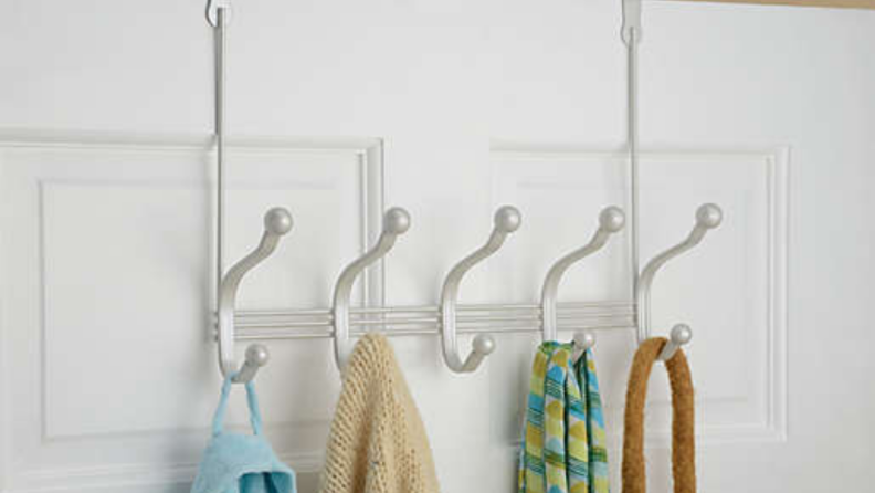 Over-the-door hooks hanging from a white door with towels and robes.