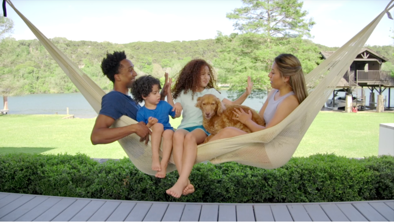 Family of four lounging in large hammock outdoors.