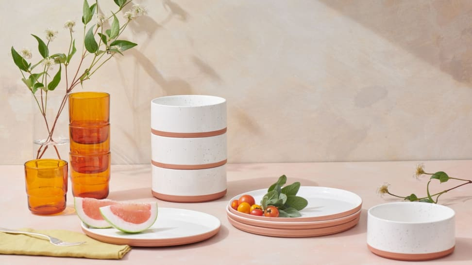 A kitchen counter covered in minimalist plates, bowls, and cups.