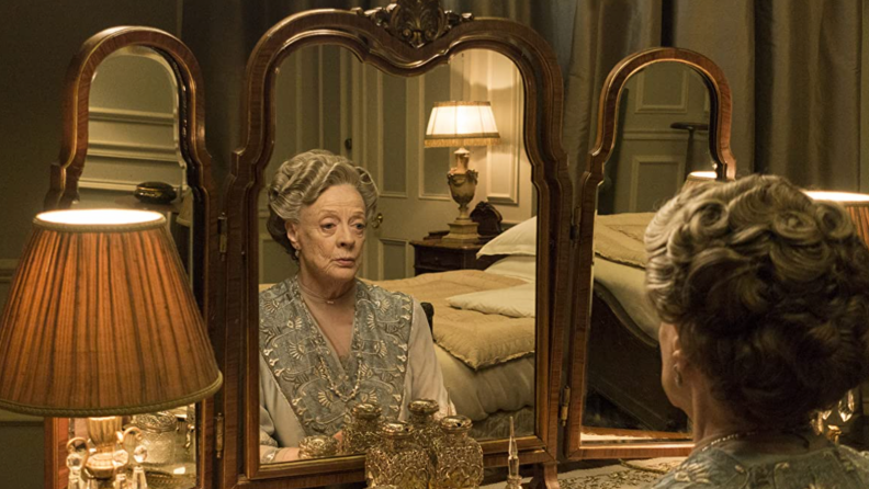 A still from Downton Abbey featuring Maggie Smith in front of a mirror.