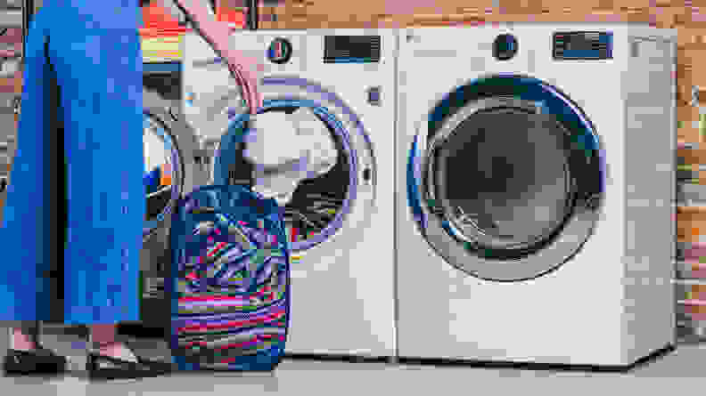 A woman placing laundry into the LG WM3700HWA washer.