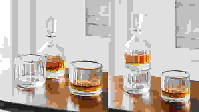 Two whiskey glasses next to decanter on wooden table