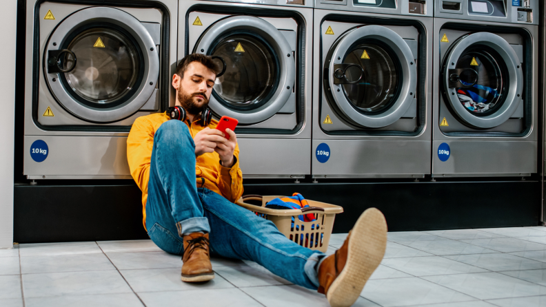 A person sets a timer on their cell phone while waiting for laundry in a laundromat.