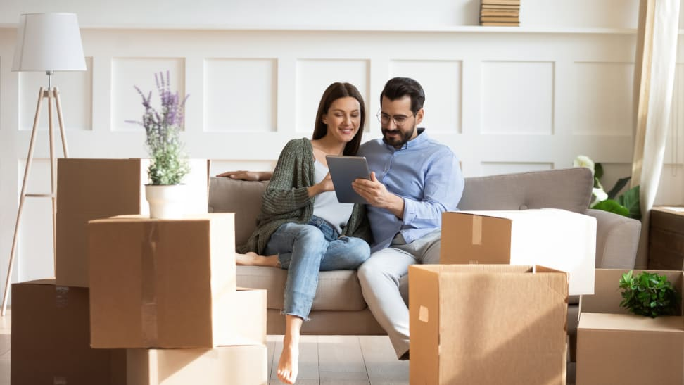 Couple sitting on couch with boxes surrounding them.