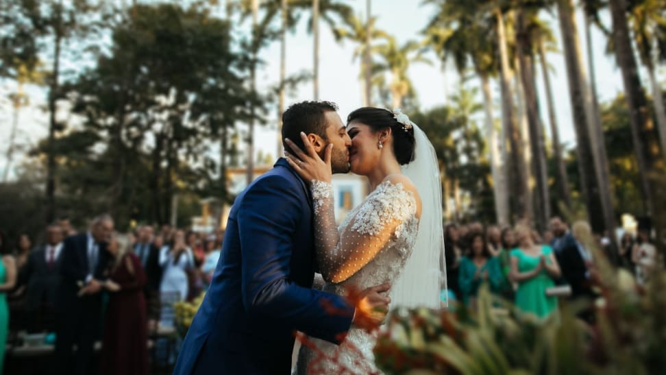 A bride and groom kiss in front of wedding guests with palm trees in the background