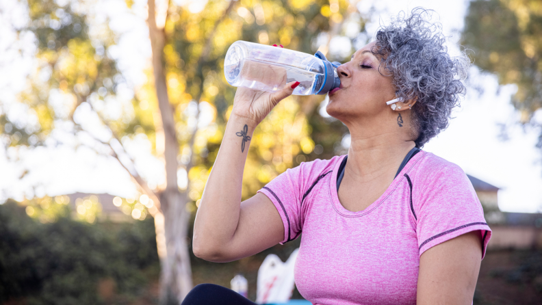 A person drinks from a plastic bottle while on a hike.
