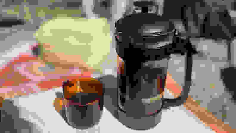 French press on table beside coffee mug.