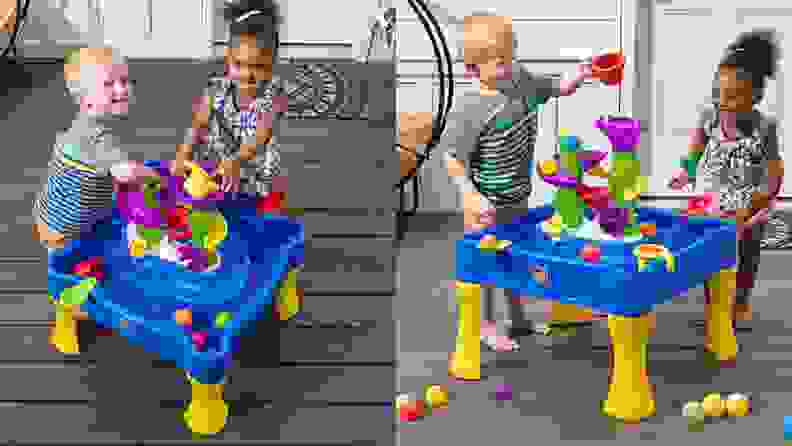 Two small children play with a water table