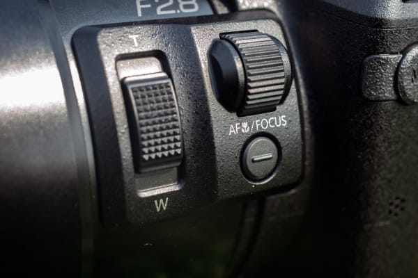 The left side of the lens has a handy focus dial and a second zoom slider–which seems unnecessary given the zoom lever attached to the shutter.