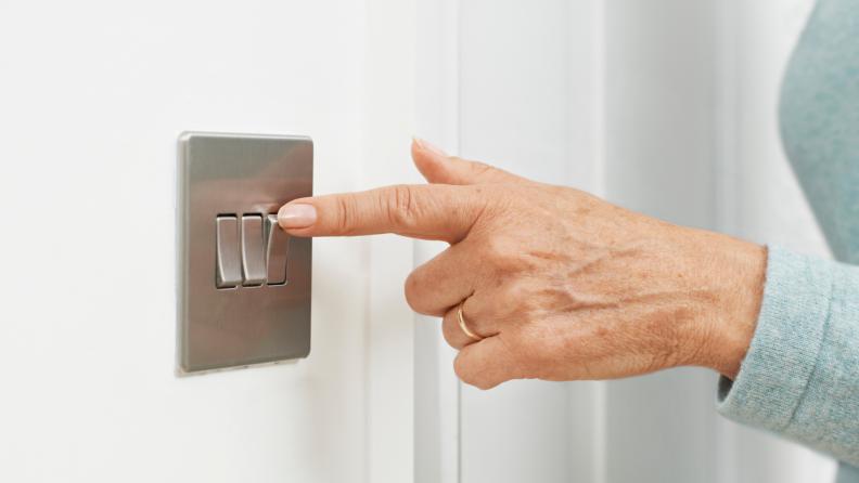 Hand of senior woman flipping toggle light switch.